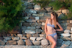 Femme dans des vêtements de bain au mur en pierre Image stock