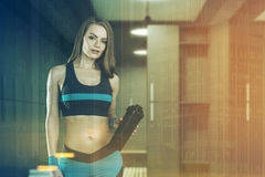 Femme dans des vêtements de sport dans le vestiaire modifié la tonalité Image stock