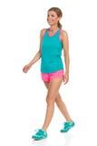 Femme dans des vêtements de sport marchant et regardant loin Image stock