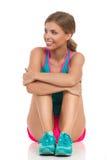 Femme dans des vêtements de sports se reposant sur le plancher et l'observation Photos libres de droits