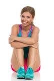 Femme dans des vêtements de sports se reposant sur le plancher Front View image stock
