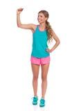 Femme dans des vêtements vibrants de sports écrivant Front View Image stock