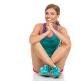 Femme dans des vêtements vibrants de sports se reposant sur le plancher Front View Photographie stock libre de droits
