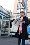 Femme dans l'écharpe rose étudiant soigneusement le journal Photos stock