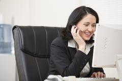 Femme dans l'écouteur fonctionnant à l'ordinateur Image stock