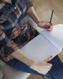 Femme dans l'écriture de chemise de plaid dans le carnet vide Photo libre de droits
