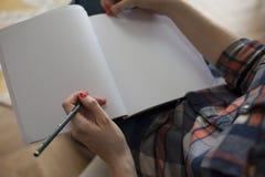 Femme dans l'écriture de chemise de plaid dans le carnet vide Images stock