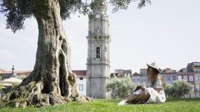Femme dans l'écriture de robe dans le carnet sous l'arbre en parc banque de vidéos