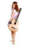 Femme dans l'équipement de hippie marchant avec la guitare Image libre de droits