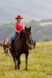 Femme dans l'équitation rouge de chapeau photos stock
