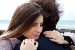 Femme dans l'amour étreignant le mari fort devant l'océan Photo libre de droits