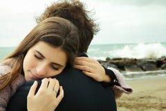 Femme dans l'amour étreignant le tir moyen heureux d'ami Image stock
