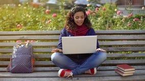 Femme dans l'amour parlant avec l'ami par l'intermédiaire de la causerie visuelle en ligne sur le banc dehors Image stock