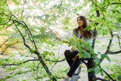 Femme dans l'arbre ayant le temps d'amusement Photographie stock