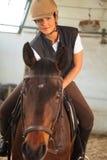 Femme dans l'arène d'intérieur d'équitation Photographie stock libre de droits