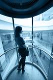Femme dans l'ascenseur en verre Photos libres de droits