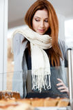 Femme dans l'écharpe regardant l'hublot de boulangerie Image libre de droits