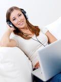 Femme dans l'écouteur avec l'ordinateur portatif Photos stock