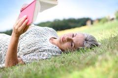 Femme dans l'herbe lisant un livre Images stock