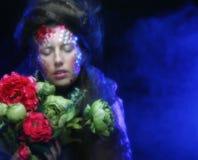 Femme dans l'image créative avec de grandes fleurs Photographie stock libre de droits