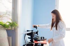 Femme dans l'image de transfert thermique de laboratoire blanc photos stock
