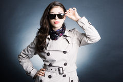 Femme dans l'imperméable et les lunettes de soleil Photographie stock libre de droits