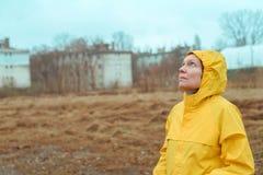 Femme dans l'imperméable jaune regardant les nuages pluvieux image libre de droits
