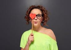Femme dans l'oeil du cache un en verre avec le coeur rouge Images stock