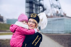 Femme dans l'uniforme noir de gala du mineur avec son enfant Photographie stock libre de droits