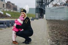 Femme dans l'uniforme noir de gala du mineur avec son enfant Image stock