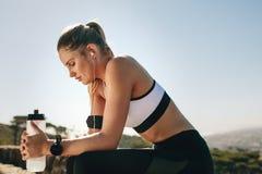 Femme dans l'usage de forme physique détendant après séance d'entraînement image libre de droits