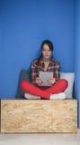Femme dans la boîte crative travaillant au comprimé Image stock