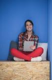 Femme dans la boîte crative travaillant au comprimé Photo stock