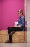 Femme dans la boîte crative travaillant sur l'ordinateur portable Photos stock