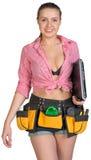 Femme dans la ceinture d'outil, tenant l'ordinateur portable sous elle Photographie stock libre de droits