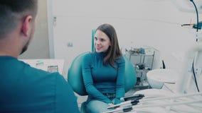 Femme dans la chaise dentaire Patient dans une clinique dentaire avec le docteur banque de vidéos
