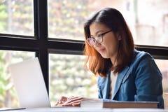 Femme dans la chemise bleue souriant à côté de la fenêtre Photo libre de droits