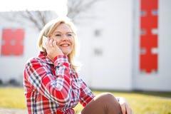 Femme dans la chemise de flanelle appelant extérieur photos stock
