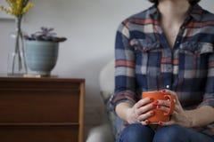 Femme dans la chemise de plaid tenant une tasse orange Image stock