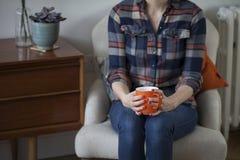 Femme dans la chemise de plaid tenant une tasse orange Photos libres de droits