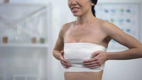 Femme dans la compression de sein d'elasto-ajustement touchant l'enveloppe, douleur se sentante après chirurgie banque de vidéos