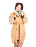 Femme dans la couche beige d'automne avec l'écharpe verte Images stock