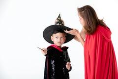 Femme dans la couverture rouge avec le capot prenant le soin pour le garçon dans des dres de costume photos libres de droits