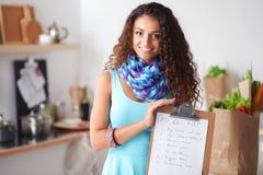 Femme dans la cuisine à la maison, tenant le bureau proche avec le dossier Photographie stock libre de droits
