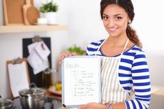 Femme dans la cuisine à la maison, tenant le bureau proche avec le dossier Images libres de droits