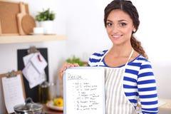 Femme dans la cuisine à la maison, tenant le bureau proche avec le dossier Femme dans la cuisine Photos stock