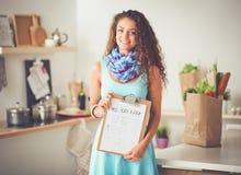Femme dans la cuisine à la maison, tenant le bureau proche avec le dossier Femme dans la cuisine image stock