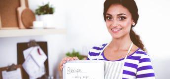 Femme dans la cuisine à la maison, tenant le bureau proche avec le dossier Femme dans la cuisine images stock