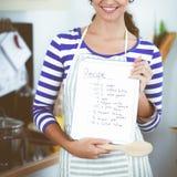 Femme dans la cuisine à la maison, tenant le bureau proche avec le dossier image stock