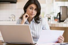 Femme dans la cuisine avec l'ordinateur portatif Photo stock